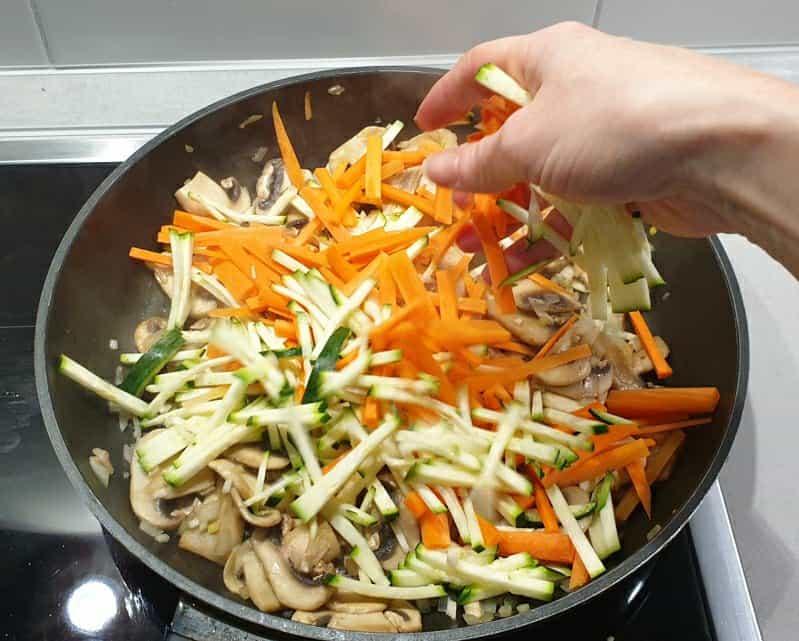 Gemüse in feine Streifen geschnitten angebraten in einer Pfanne.