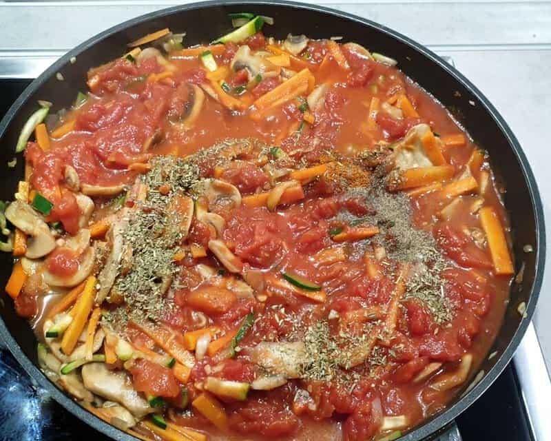 Gemüse mit gehackten Tomaten und Gewürzen in einer Pfanne.