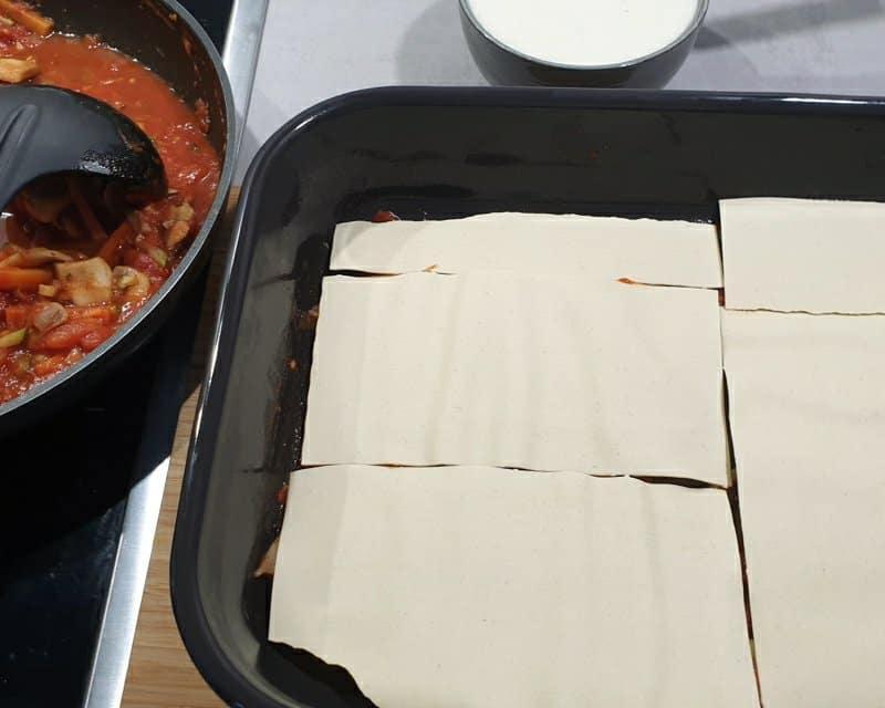 Lasagne Platten auf einer Soße in einer Auflaufform.