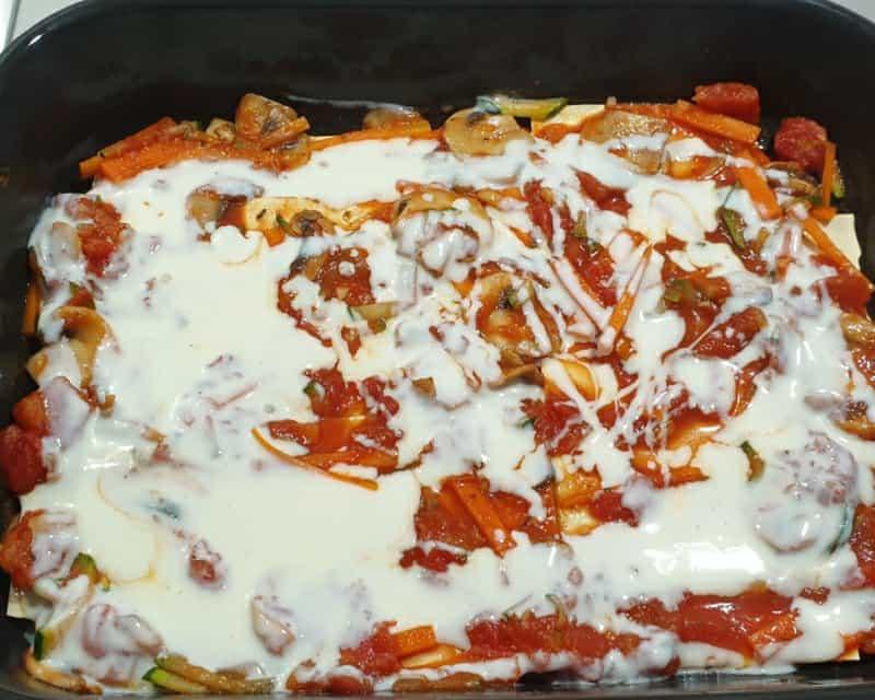 Béchamelsoße auf einer geschichteten Gemüse Lasagne.