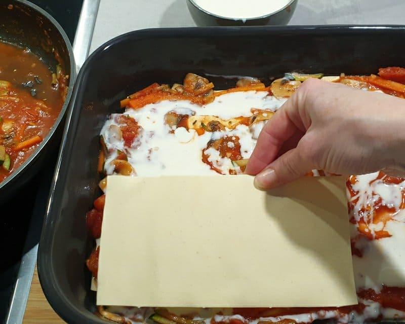 Lasagne Platten auf einer Tomatensoße mit Béchamelsoße.