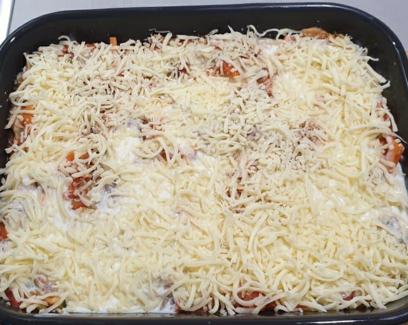 Geriebener Käse auf einer geschichteten Gemüse Lasagne in einer dunklen Auflaufform.