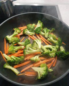 In einer Pfanne angebratene Möhren und Brokkoli Röschen in Öl.