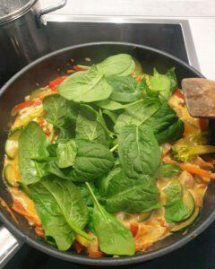Frischer Spinat mit Gemüse Curry in der Pfanne.