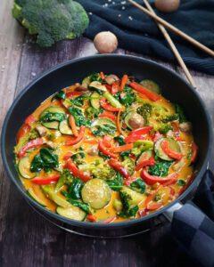 In einer Pfanne angerichtet ein Gemüse Curry mit Kokosmilch mit Sesam bestreut.