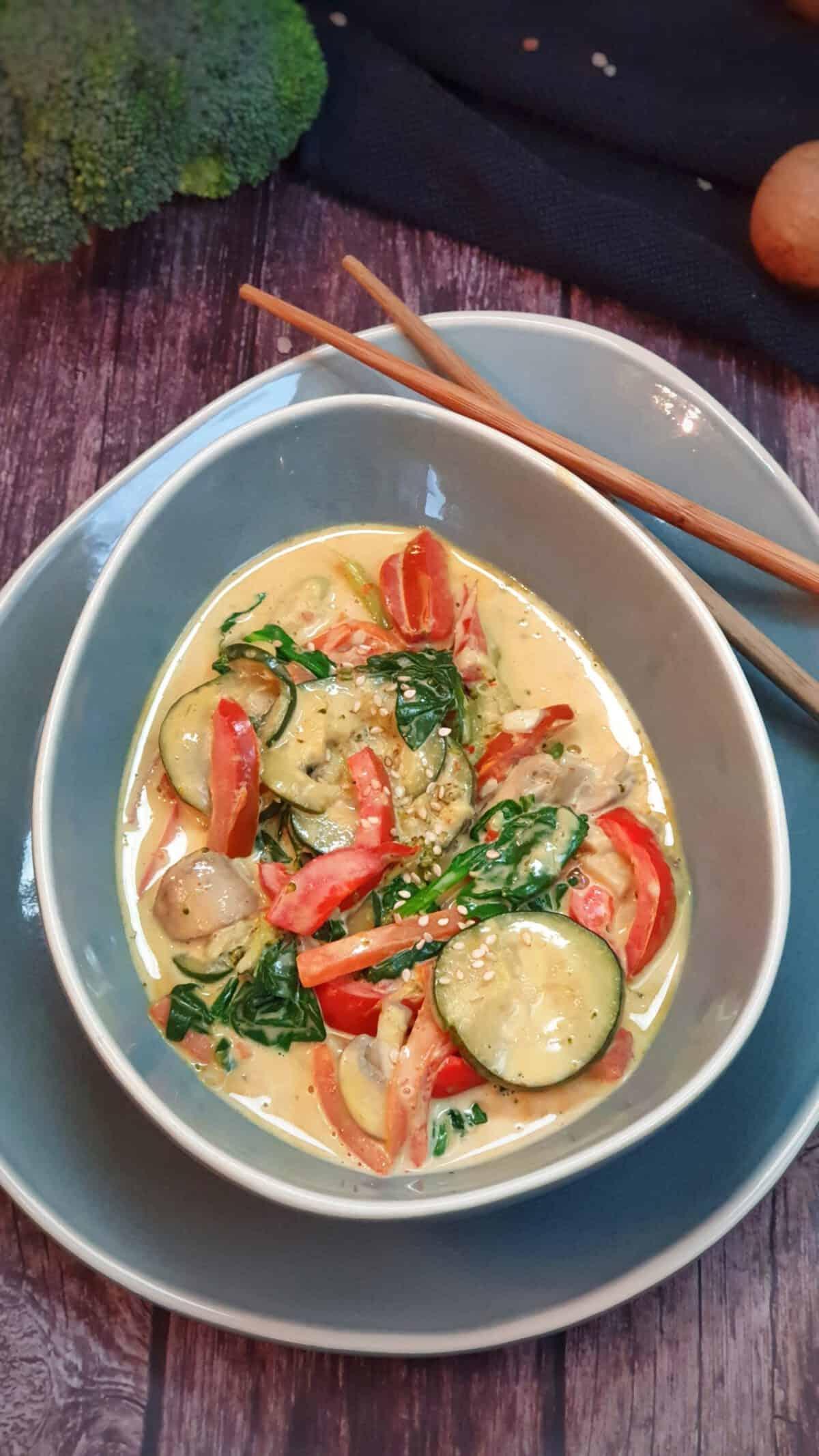 In einer graublauen ovalen Schale angerichtet Gemüse Curry mit Kokosmilch. Im Hintergrund Deko mit Essstäbchen.