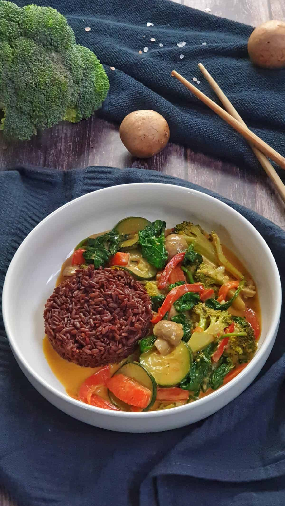 In einer weißen Schale angerichtet Gemüse-Curry mit rotem Reis.