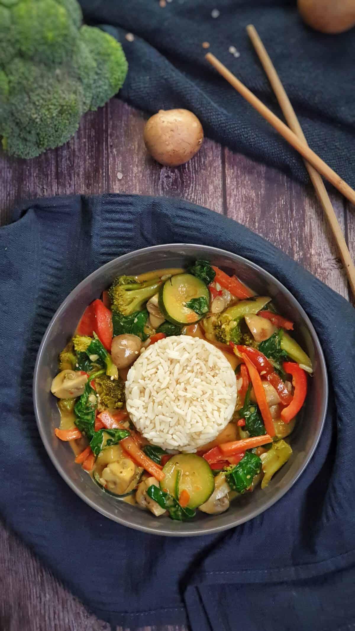 In einer grauen Schale angerichtet Gemüse-Curry mit weißem Reis.