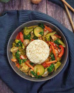 In einer grauen Schale angerichtet Gemüse Curry mit weißem Reis.