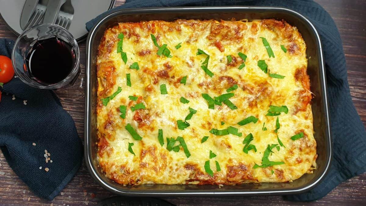 Gemüse-Lasagne mit gehacktem Basilikum bestreut in einer dunklen Auflaufform. Im Hintergrund Deko.