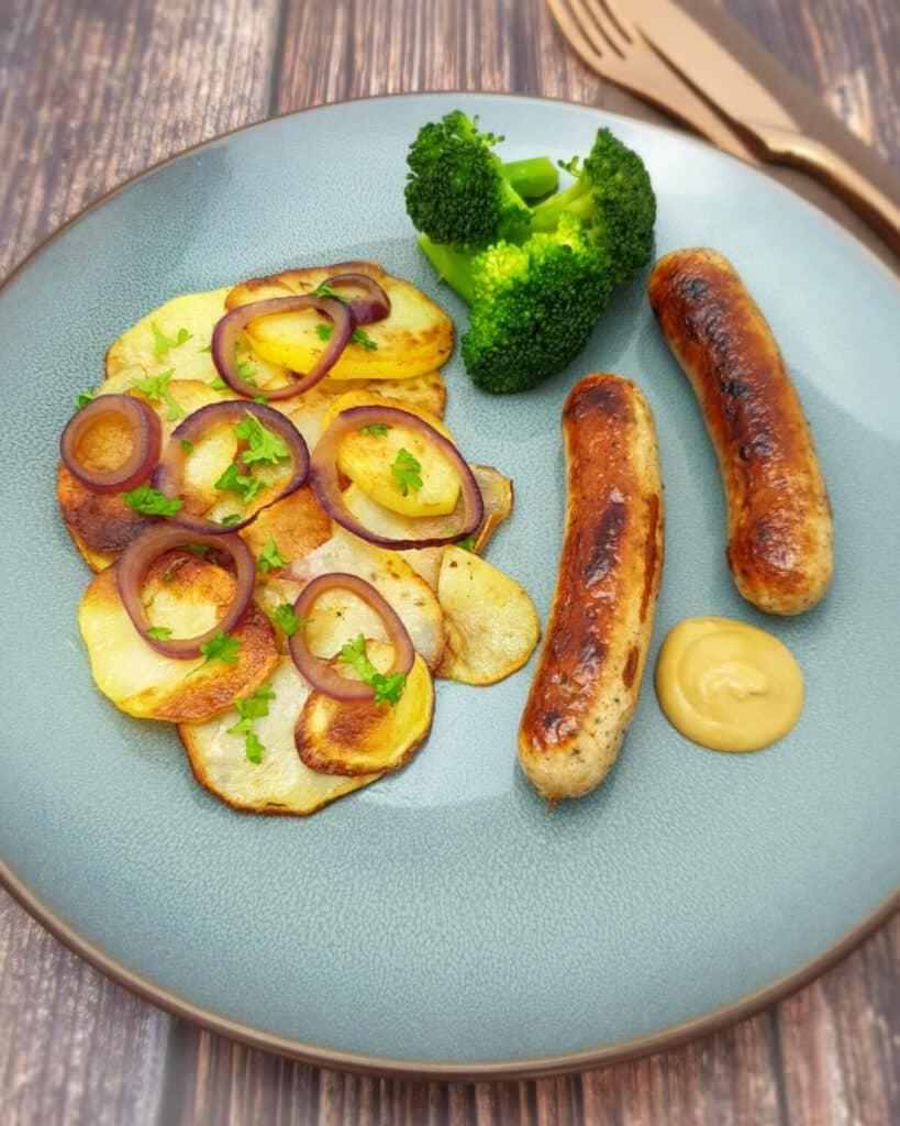 Knusprige Bratkartoffeln mit roten Zwiebel und einer Bratwurst auf einem blauen Teller.