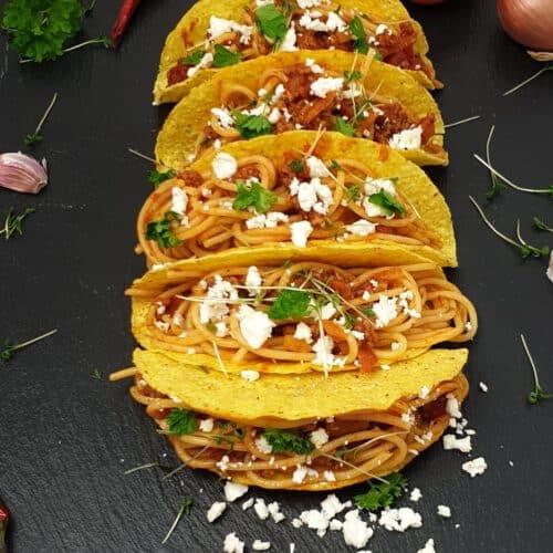Auf einer schwarzen Schieferplatte Spaghetti Tacos mit Mozzarella und Petersilie.