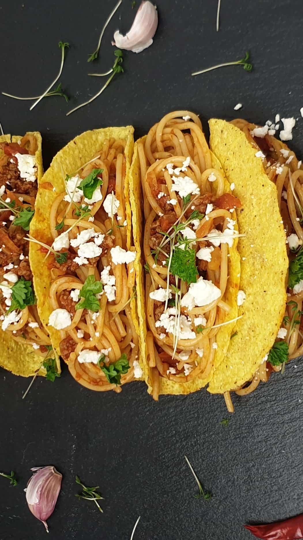 Auf einer schwarzen Schieferplatte gefüllte Tacos mit Spaghetti, Mozzarella und Petersilie.