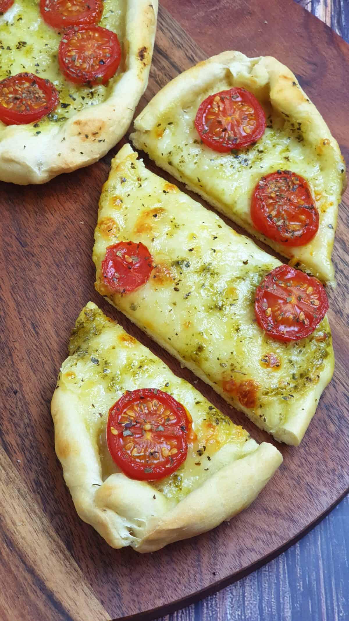 Auf einem braunen runden Brett angerichtet 2 Tomate-Mozzarella-Schiffchen. Daneben Deko und Besteck.