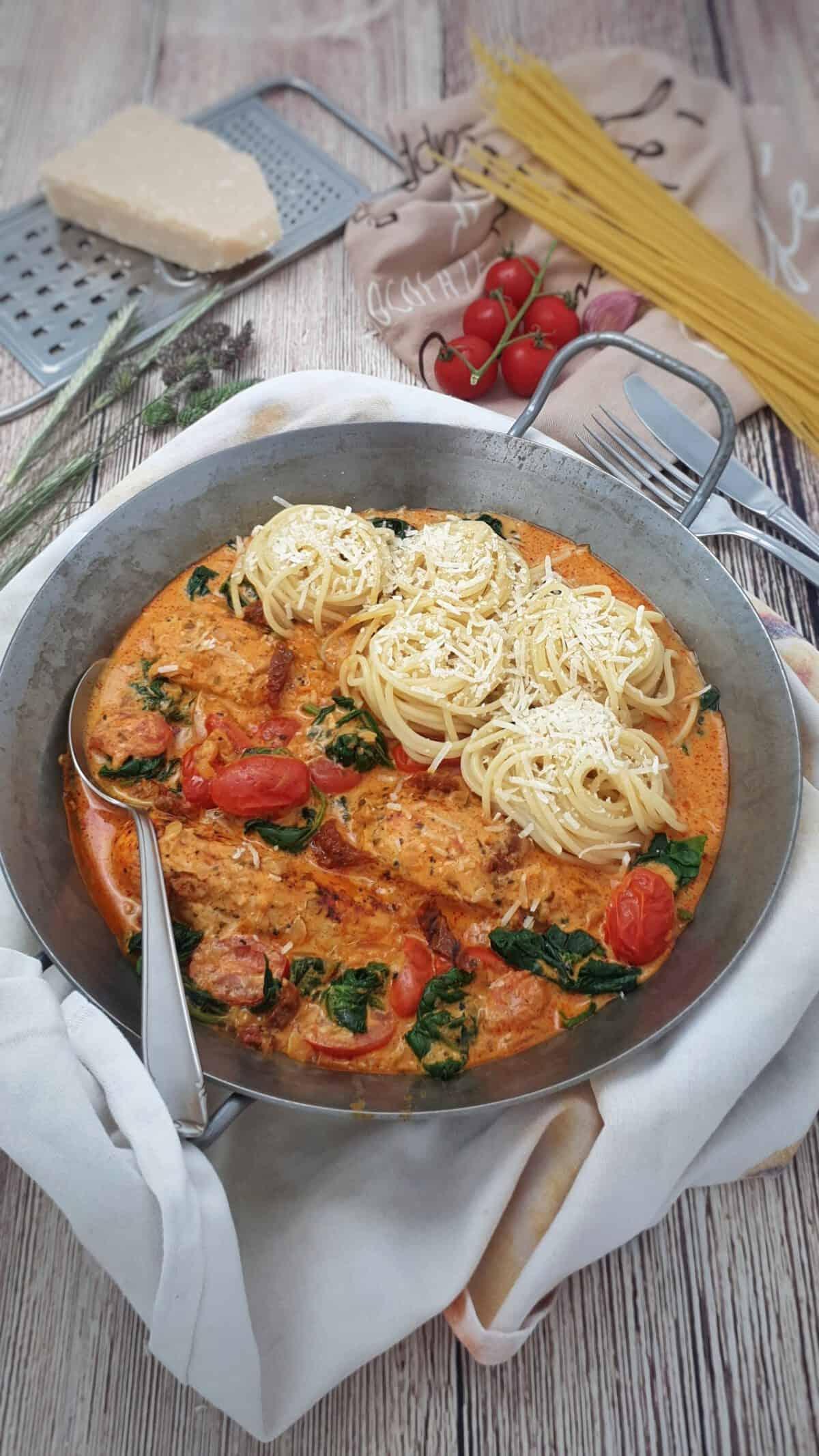 In einer eisernen Pfanne Hähnchenfilet in Parmesan-Frischkäse-Soße mit Spaghetti Nestern.