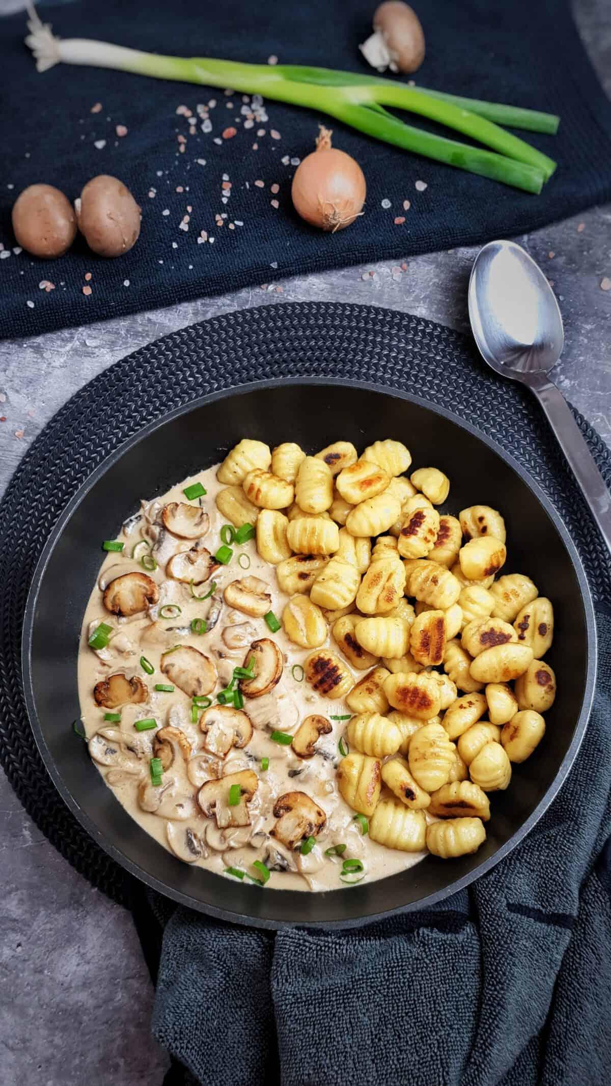 Gnocchi mit Pilzrahmsoße in einer Pfanne angerichtet und mit Schnittlauch bestreut.