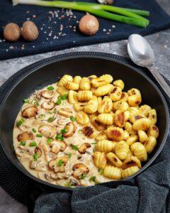 Gnocchi mit Pilz Rahm Soße in einer Pfanne angerichtet und mit Schnittlauch bestreut.