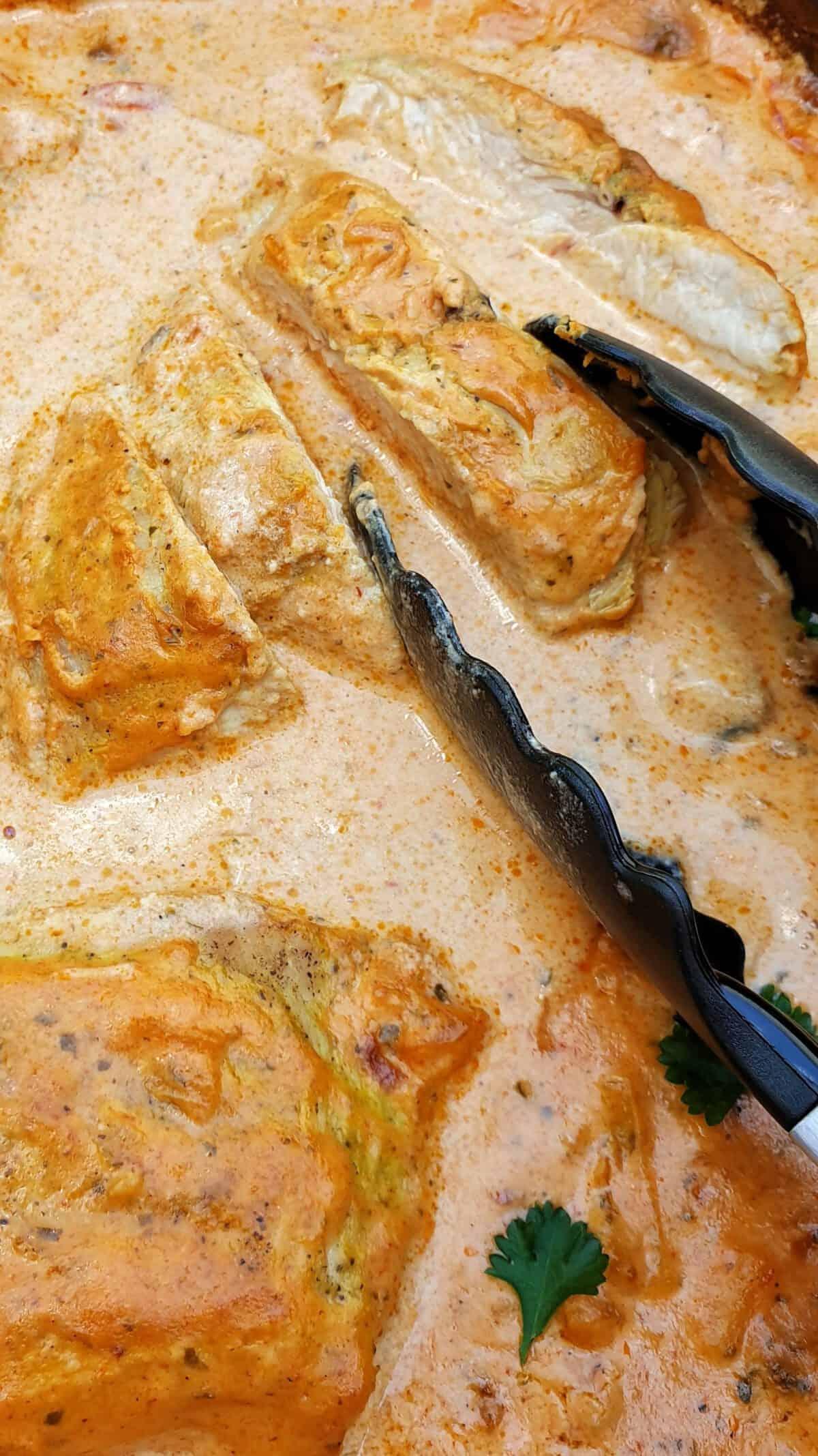 Geschnittene Putenbrust aus dem Ofen mit Soße angerichtet mit Petersilie in eine dunklen Auflaufform.