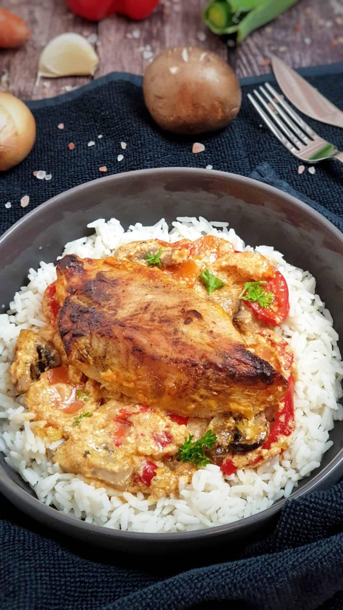 In einer grauen Schale Reis mit einem Stück Putenbrust Filet auf Frischkäse-Soße.