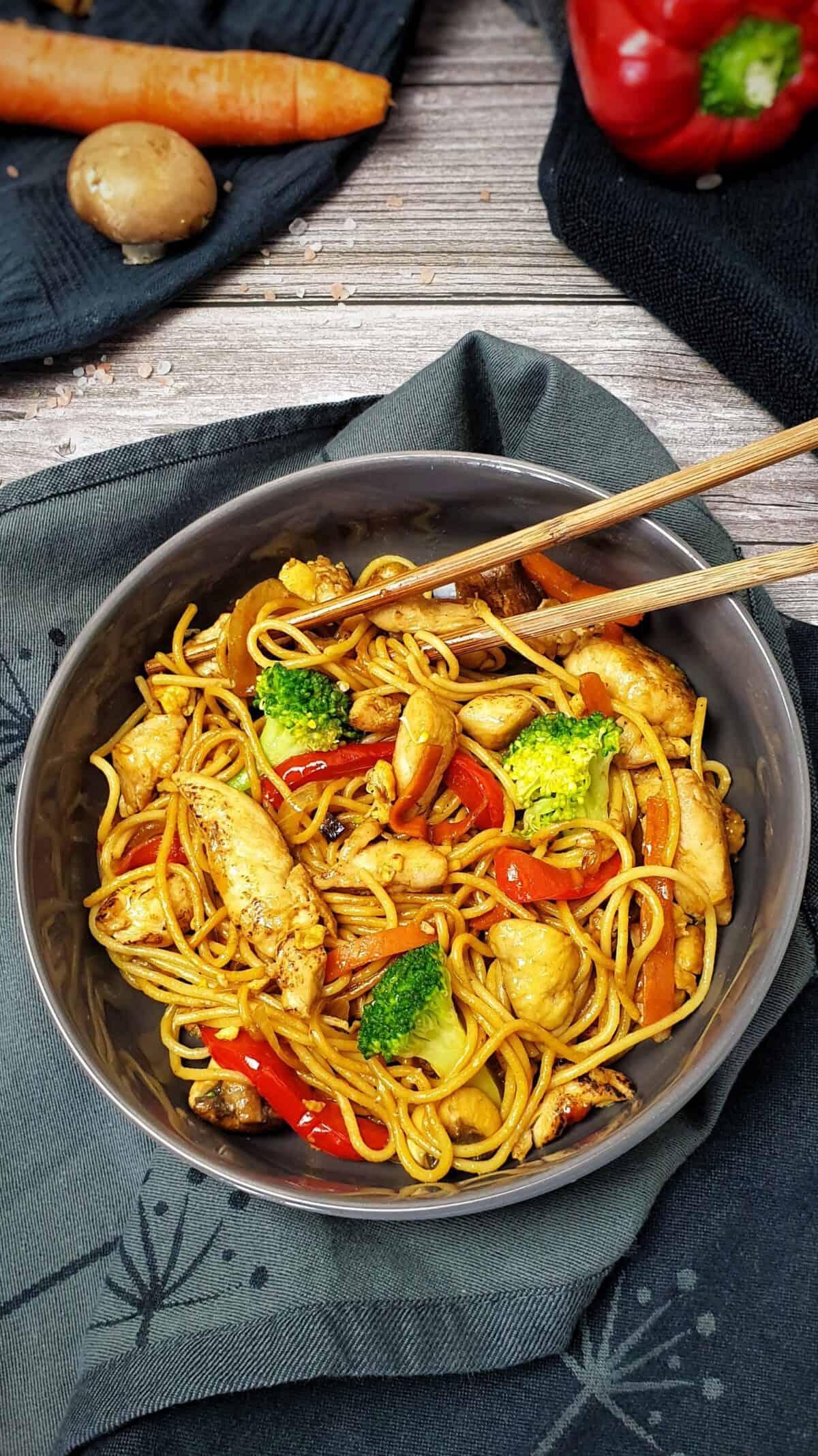 In einer grauen Schale angerichtet Asiatisch angebratene Nudeln mit Fleisch und Gemüse.