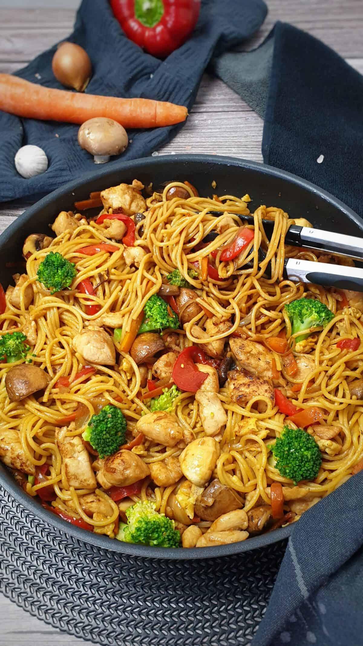 In einer Pfanne angerichtet Asia Nudelpfanne mit Gemüse und Hähnchen. Im Hintergrund Deko auf einem Küchentuch.