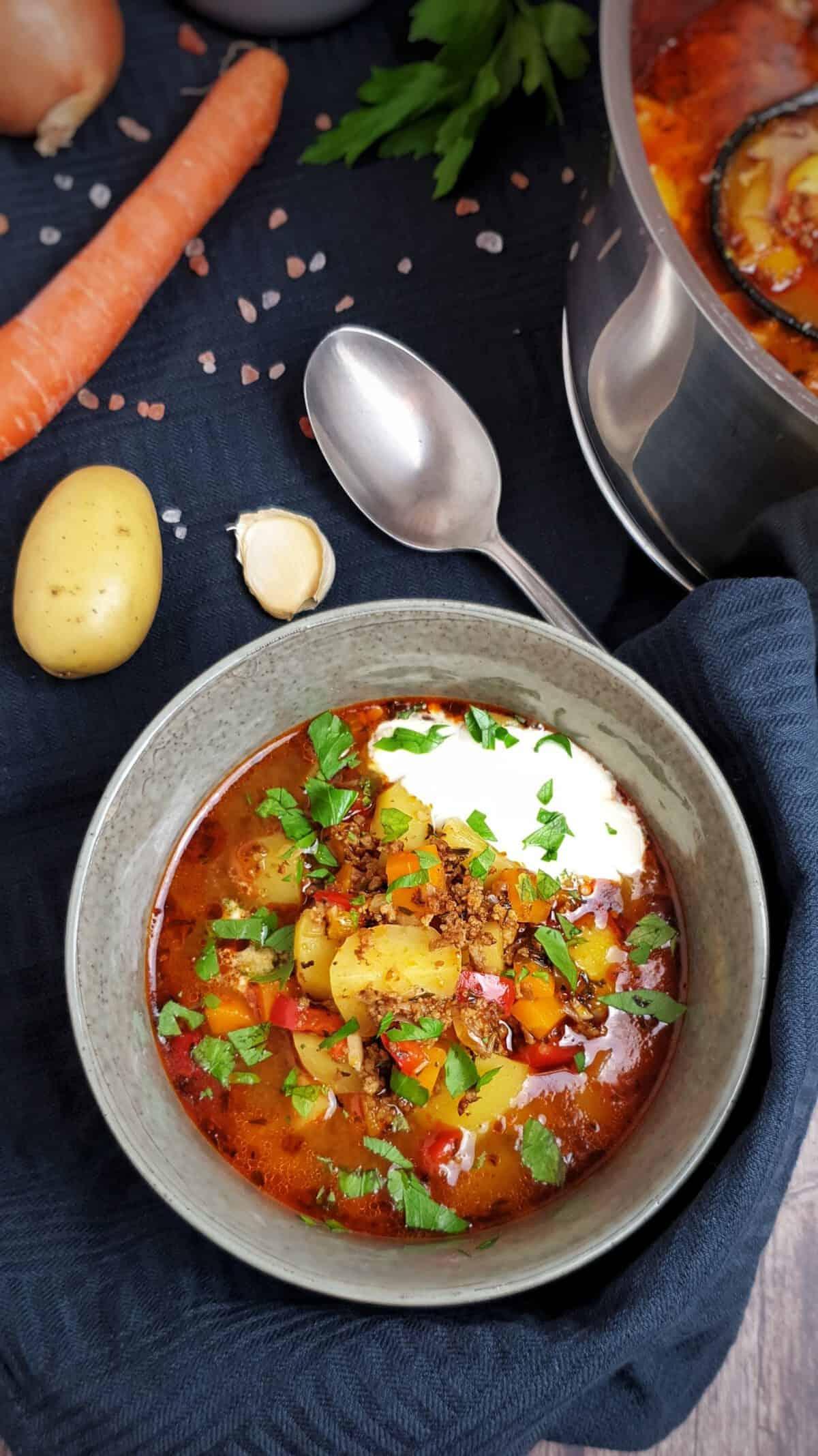 In ein grauen Schale angerichtet Bauerntopf mit Hackfleisch und Gemüse serviert mit einem Klecks Crème fraîche.