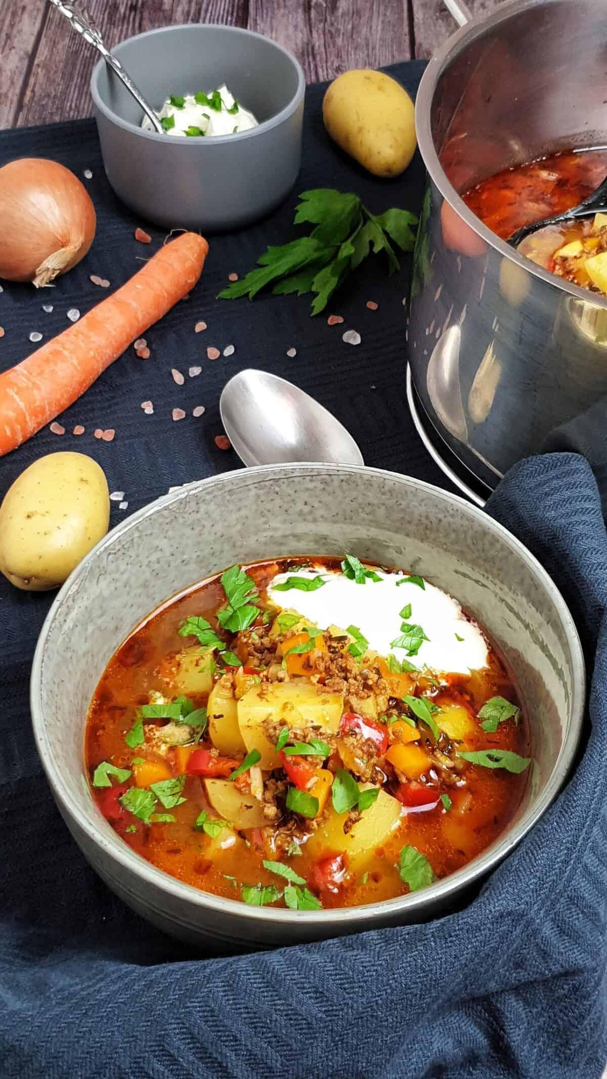 In einer grauen Schale angerichtet Eintopf Hack und Gemüse serviert mit einem Klecks Crème fraîche.