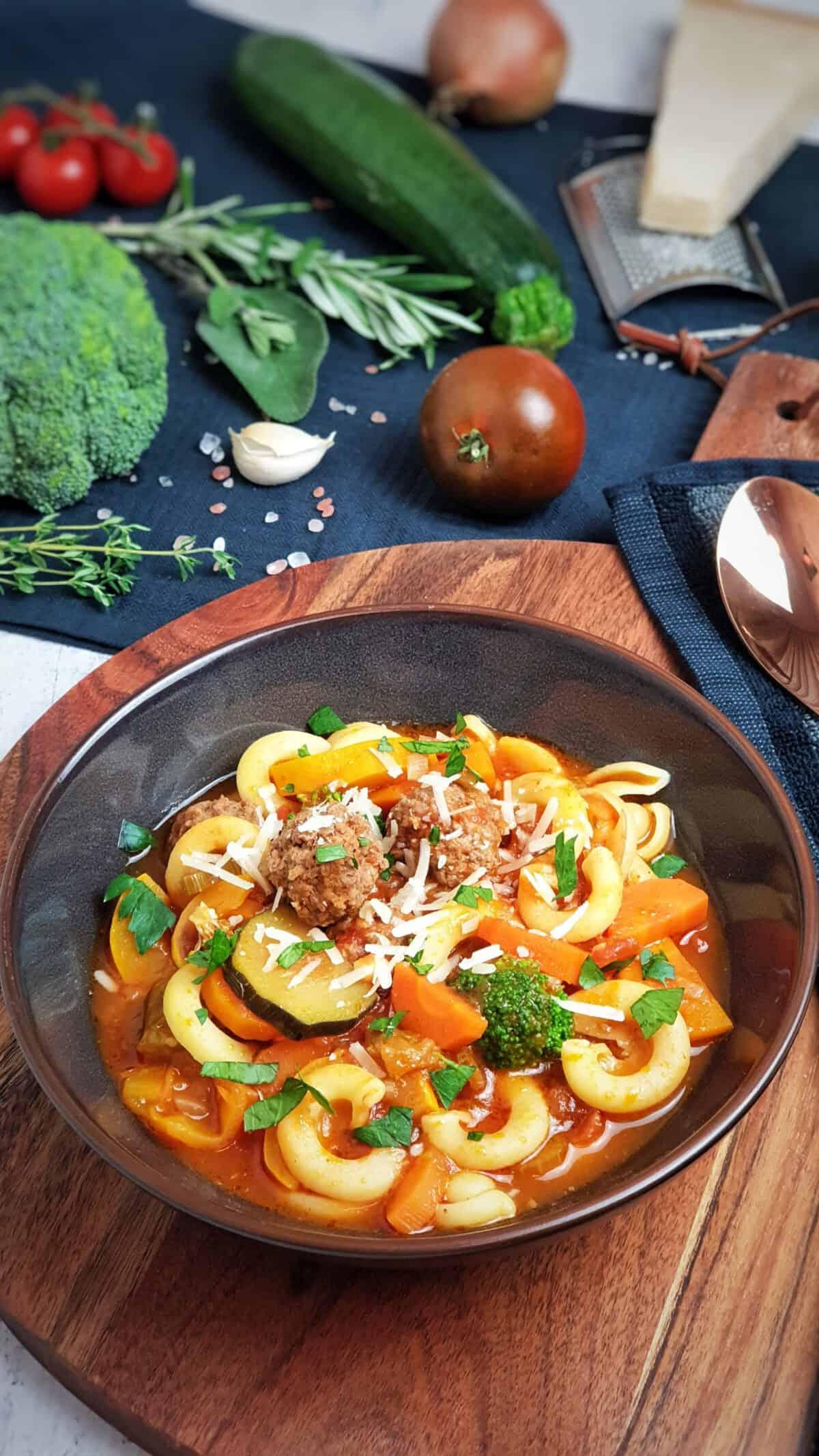 Minestrone, italienische Gemüsesuppe angerichtet in einer braunen Schale mit Parmesan bestreut. Im Hintergrund Deko.
