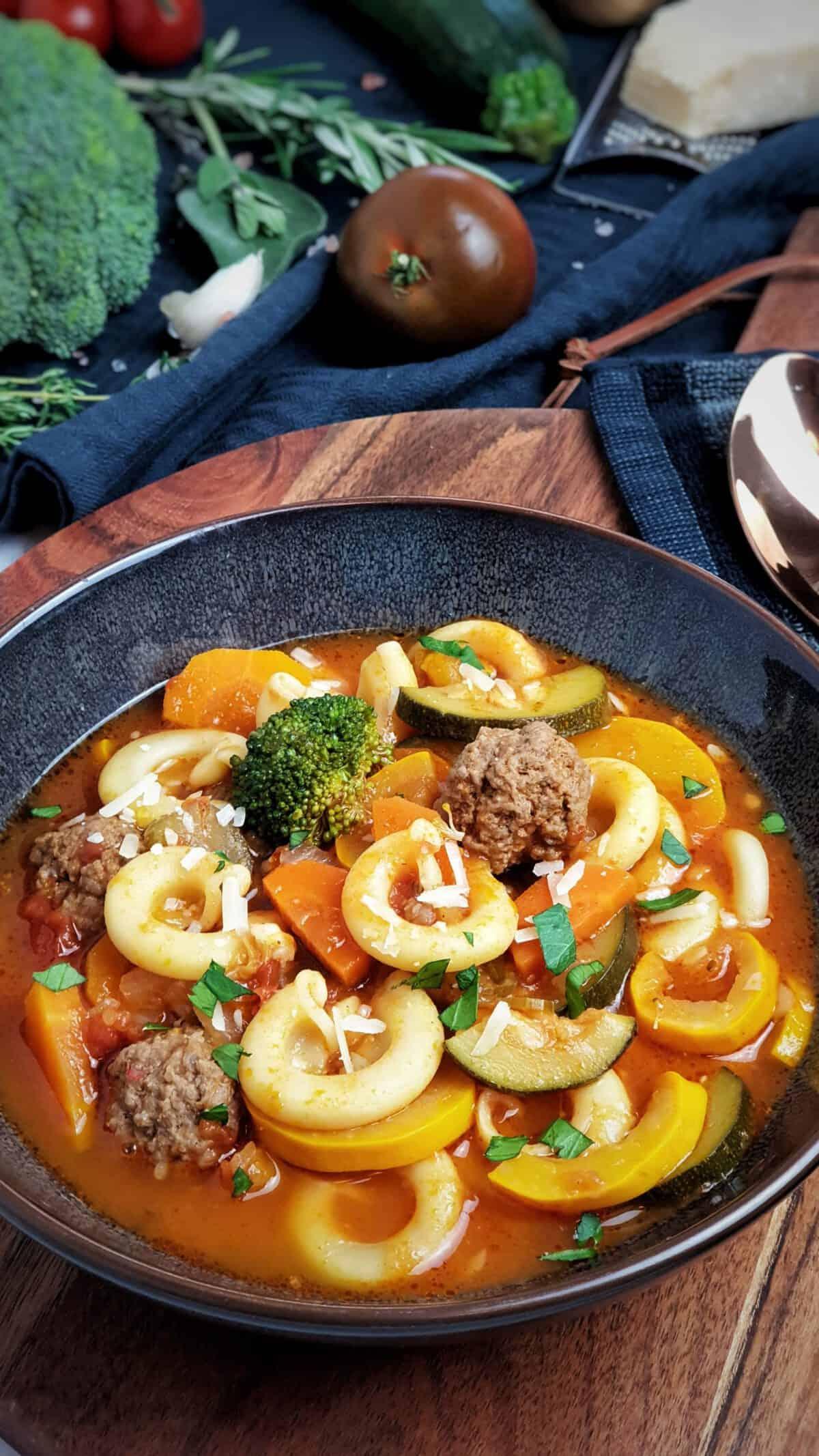 Minestrone, italienische Gemüsesuppe angerichtet in einer braunen Schale. Im Hintergrund Deko.