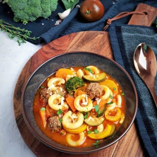 Minestrone - italienische Gemüse-Suppe angerichtet in einer braunen Schale. Im Hintergrund Deko.