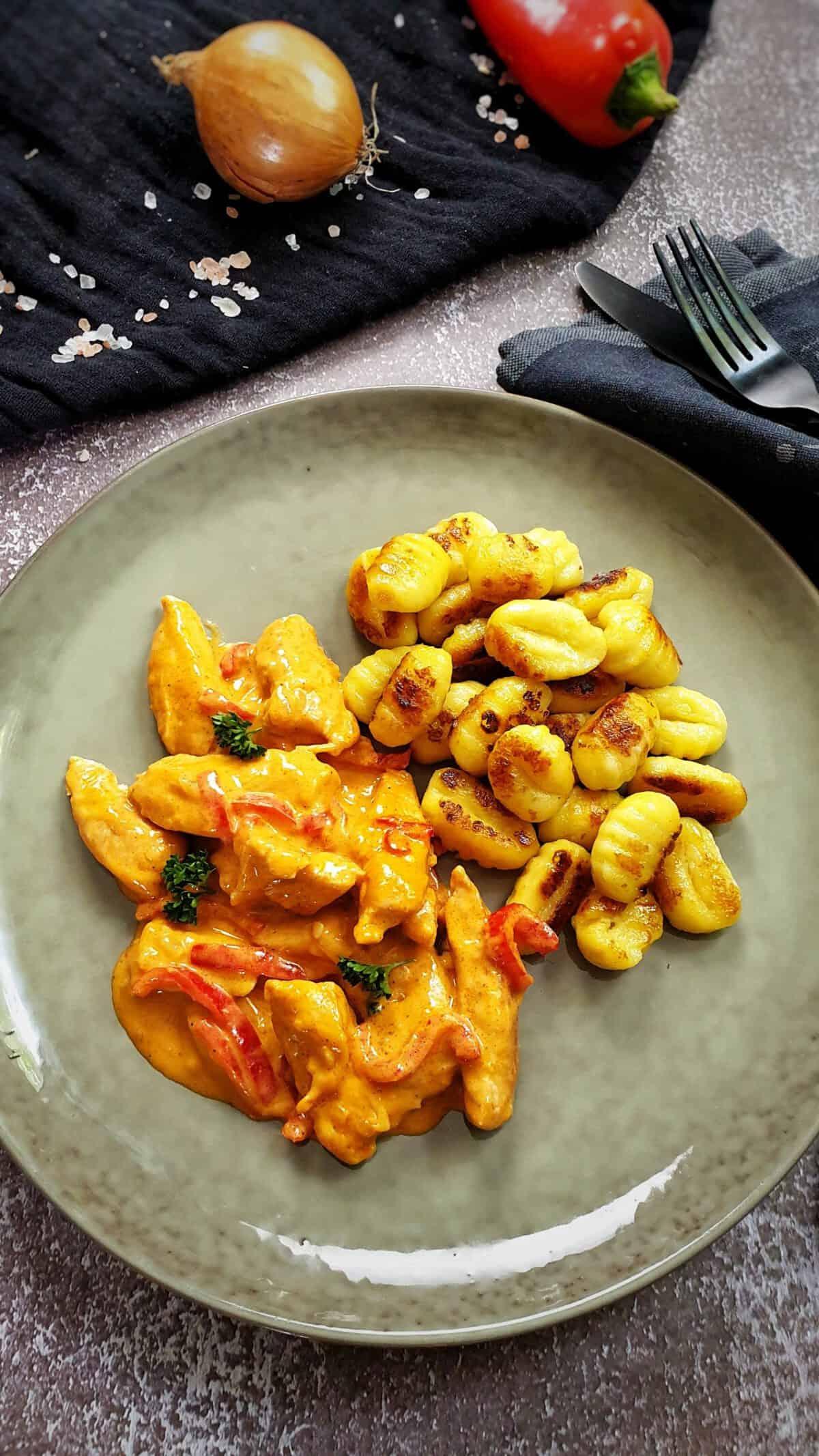 Paprika-Sahne-Hänchen mit Gnocchi auf einem grünen Teller angerichtet.