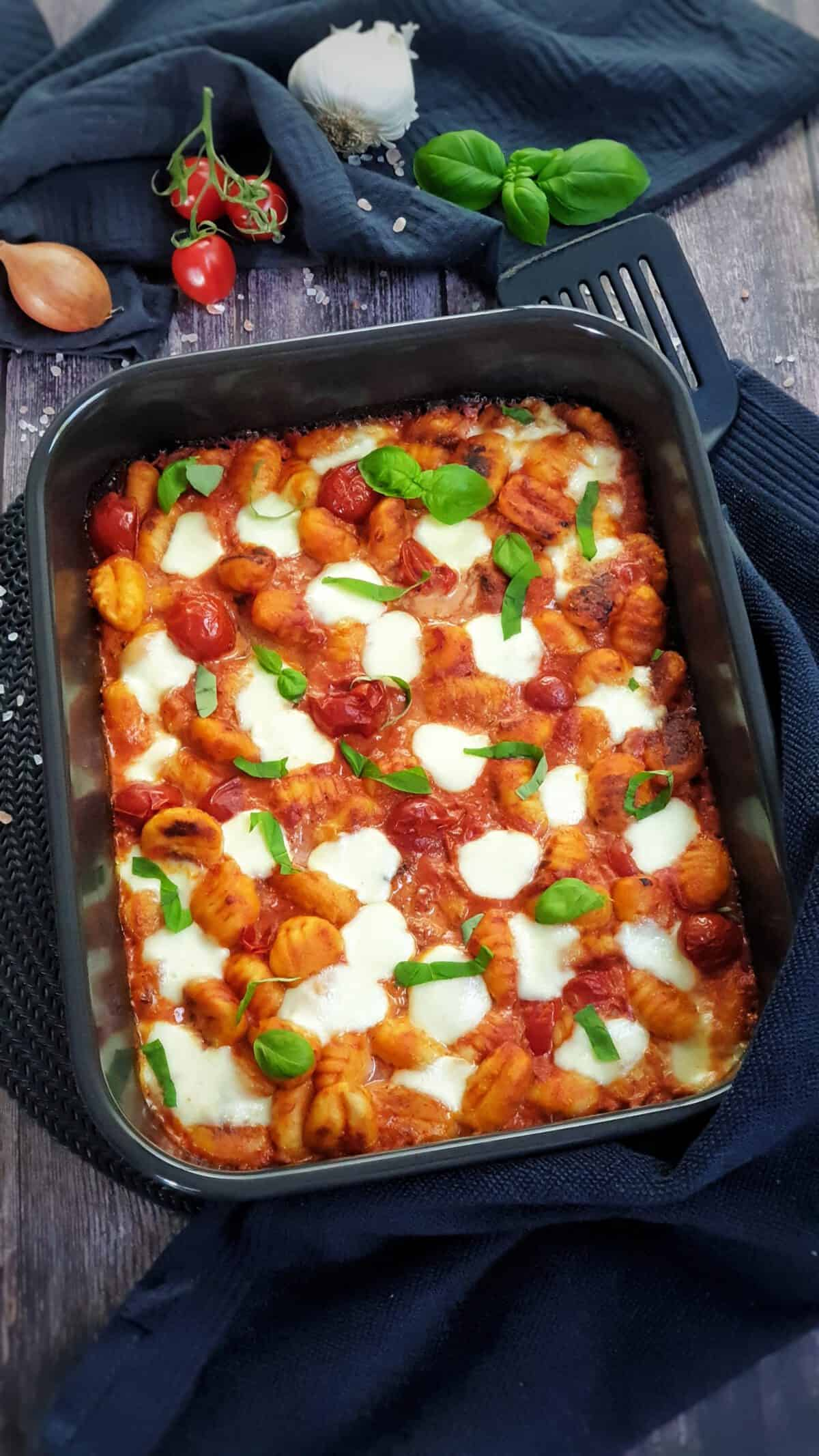 In einer dunklen Auflaufform ein Gnocchi Auflauf mit Tomate und Mozzarella überbacken. Mit Basilikum garniert. Im Hintergrund Deko.