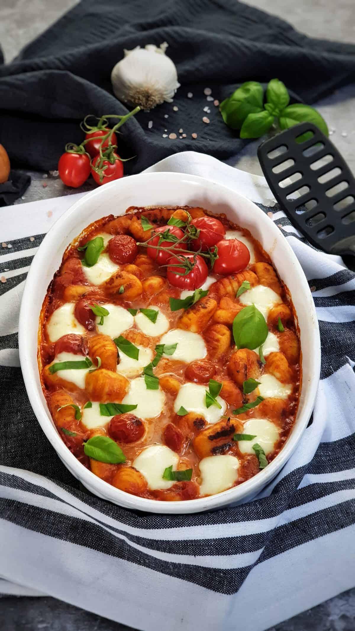Gnocchi Auflauf mit Tomate und Mozzarella, fotografiert in einer weißen Auflaufform. Im Hintergrund Deko.