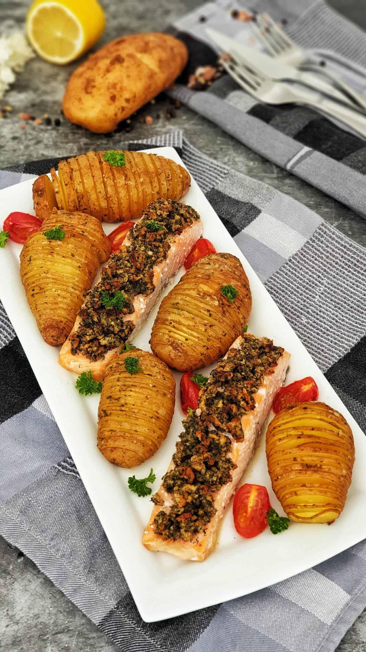 Auf einer weißen Servierplatte Lachsfilet mit Kräuterkruste und Fächerkartoffeln.