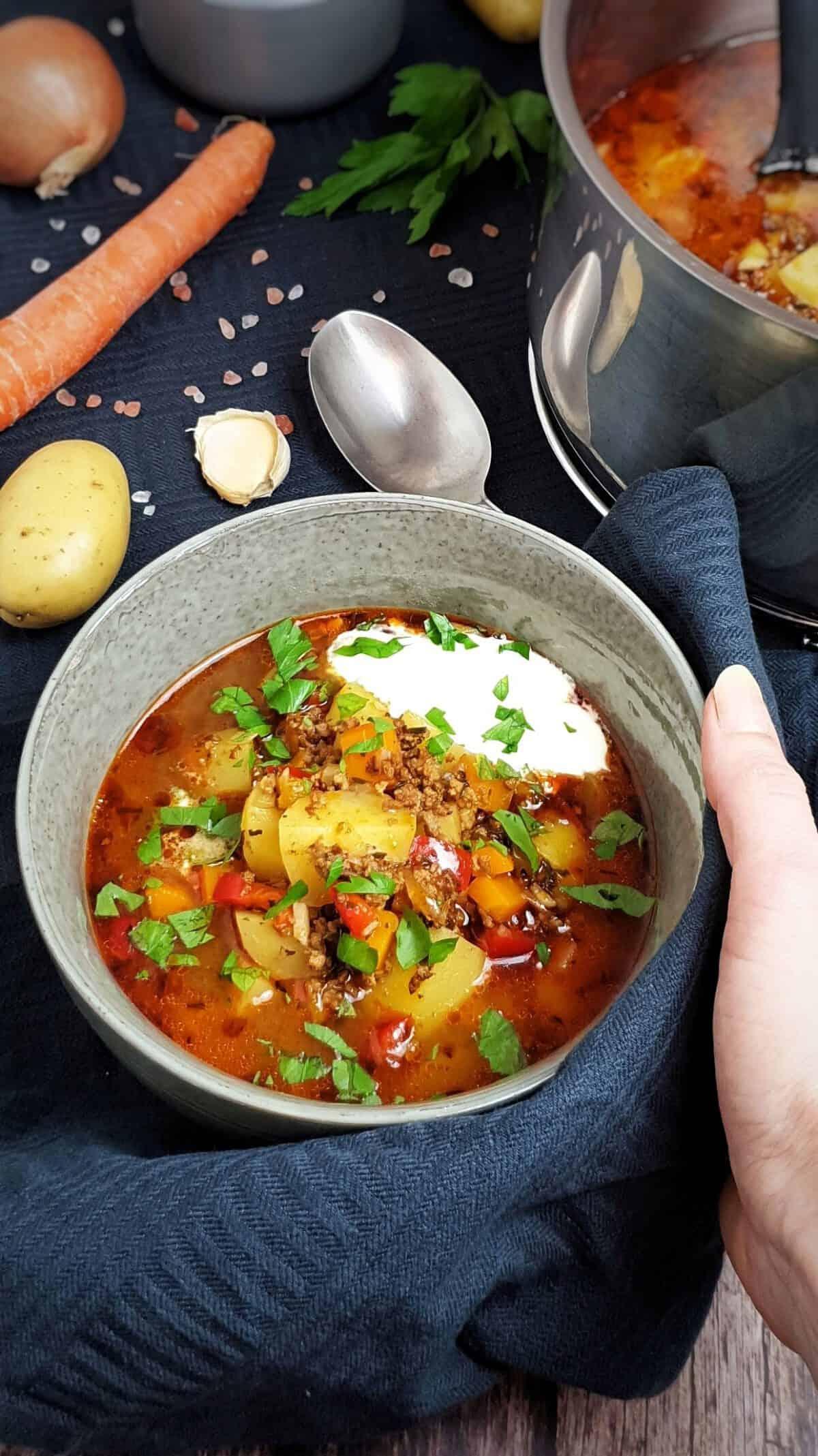 In einer grauen Schale angerichtet Bauerntopf mit Rinderhackfleisch und Gemüse serviert mit einem Klecks Crème fraîche.