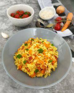 In einer grauen Schale angerichtet eine Puten-Reis-Pfanne mit Gemüse.