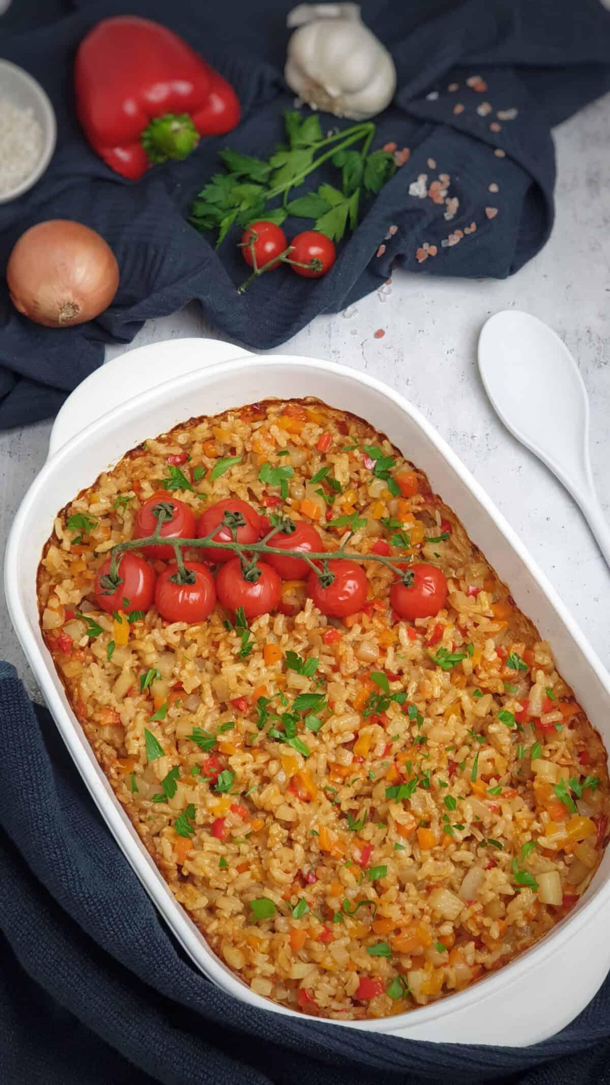 In einer weißen Auflaufform Ofen-Risotto mit Gemüse und Tomaten, mit Petersilie bestreut.