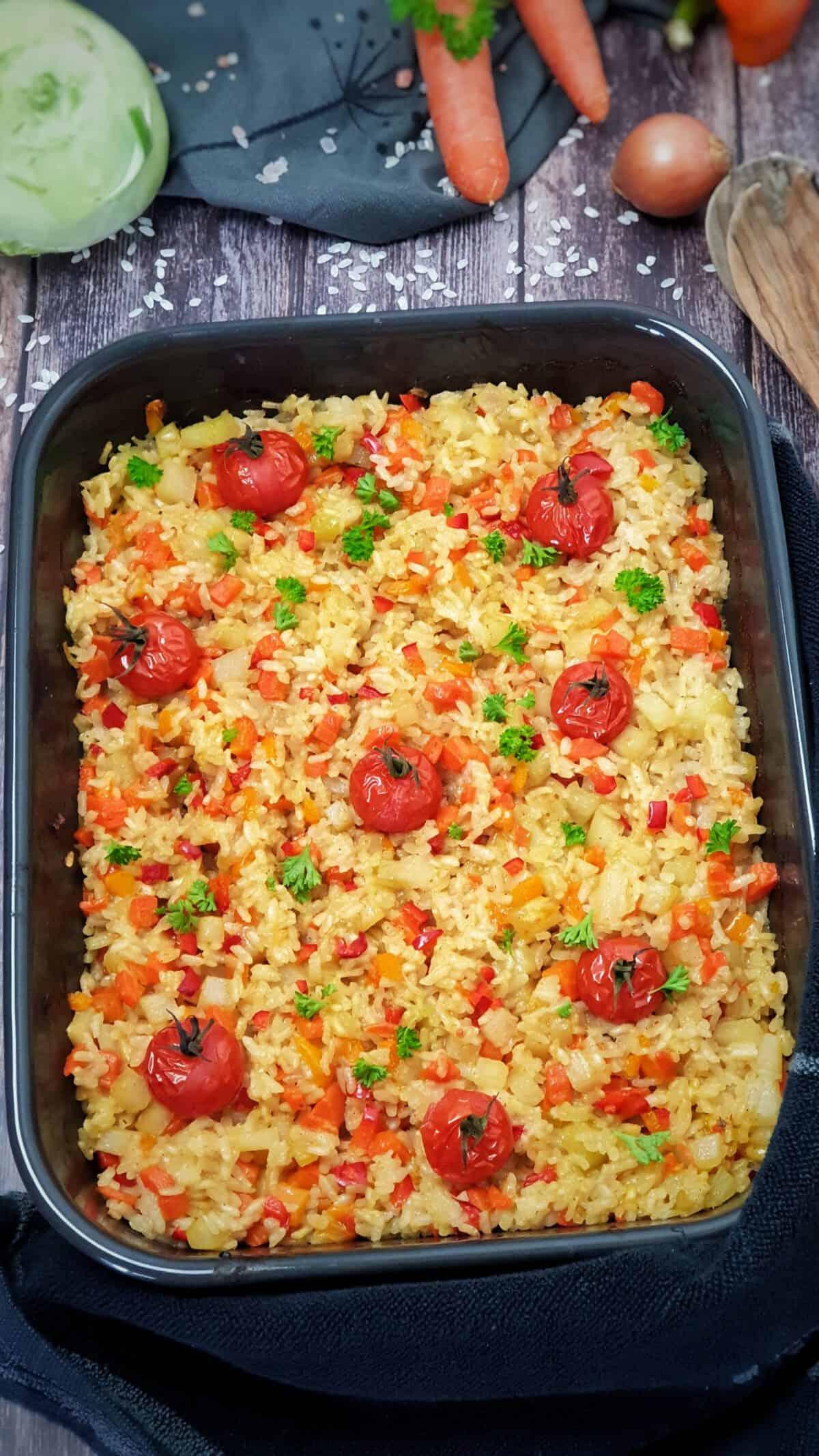 In einer dunklen Auflaufform Ofen-Risotto mit Gemüse und Tomaten, mit Petersilie bestreut.