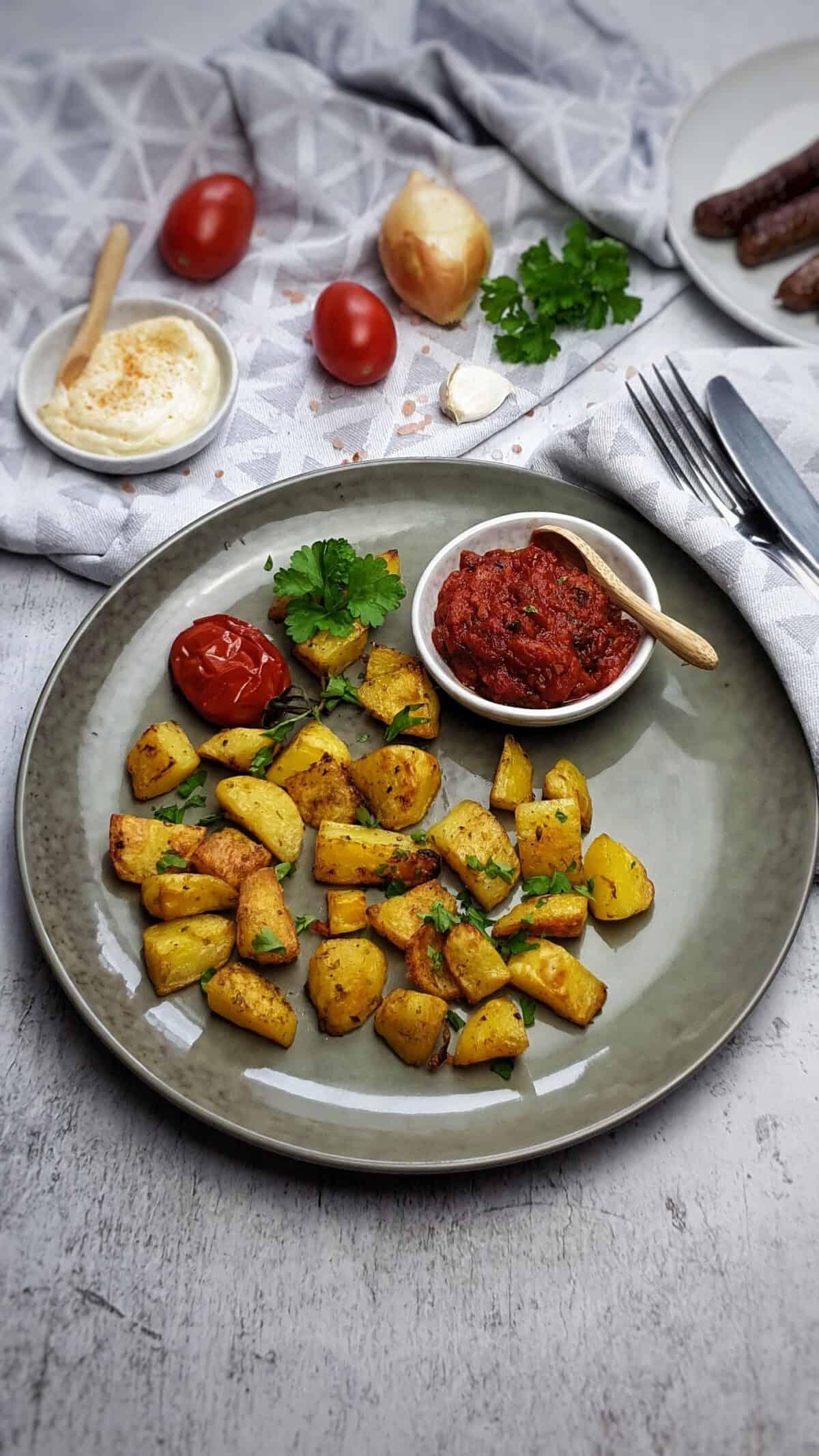 Auf einem grünen Teller Ofen Kartoffeln. Im Hintergrund Deko.