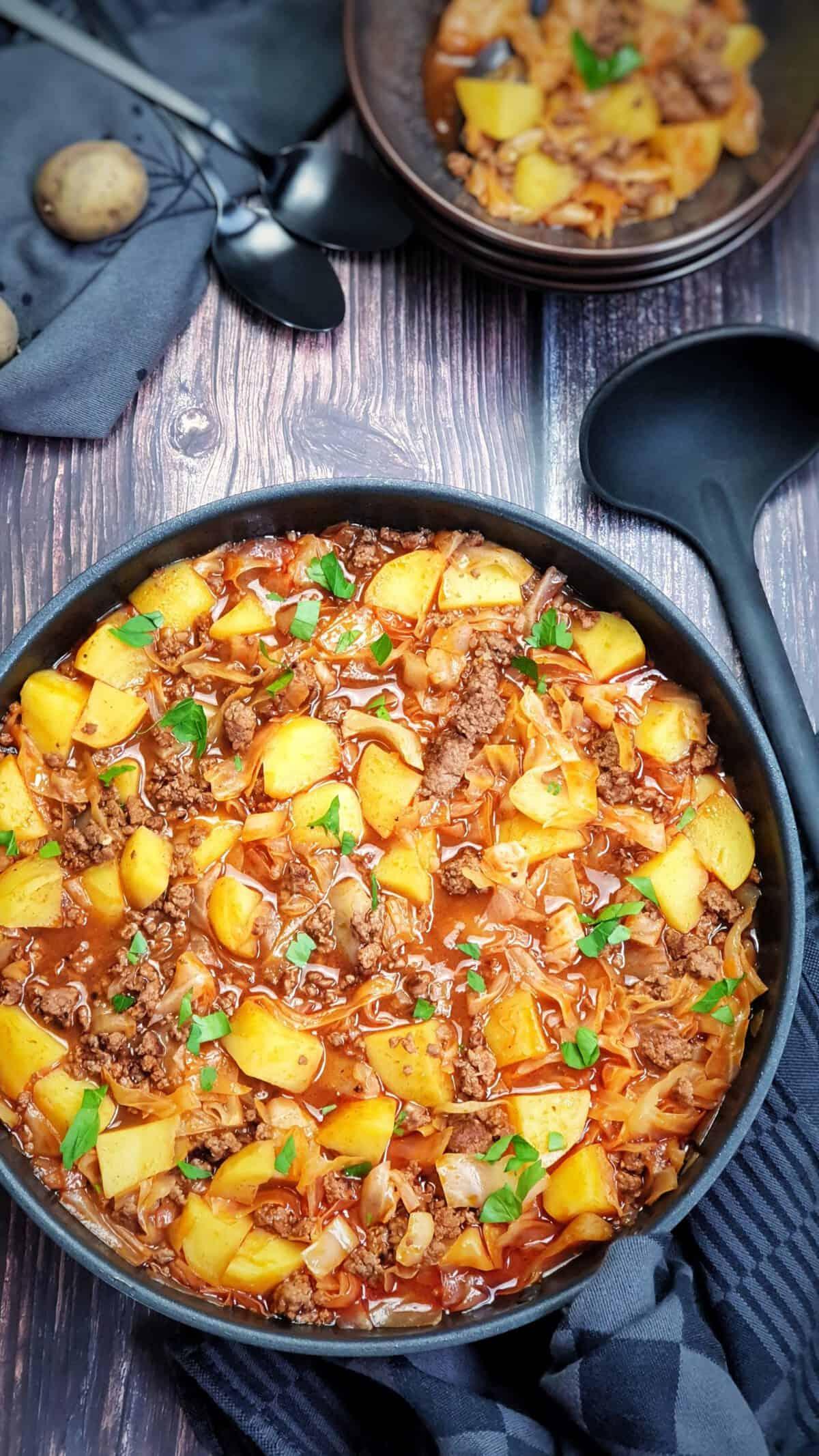 In einer schwarzen Pfanne ein Kohlgericht mit Kartoffeln und Hackfleisch.