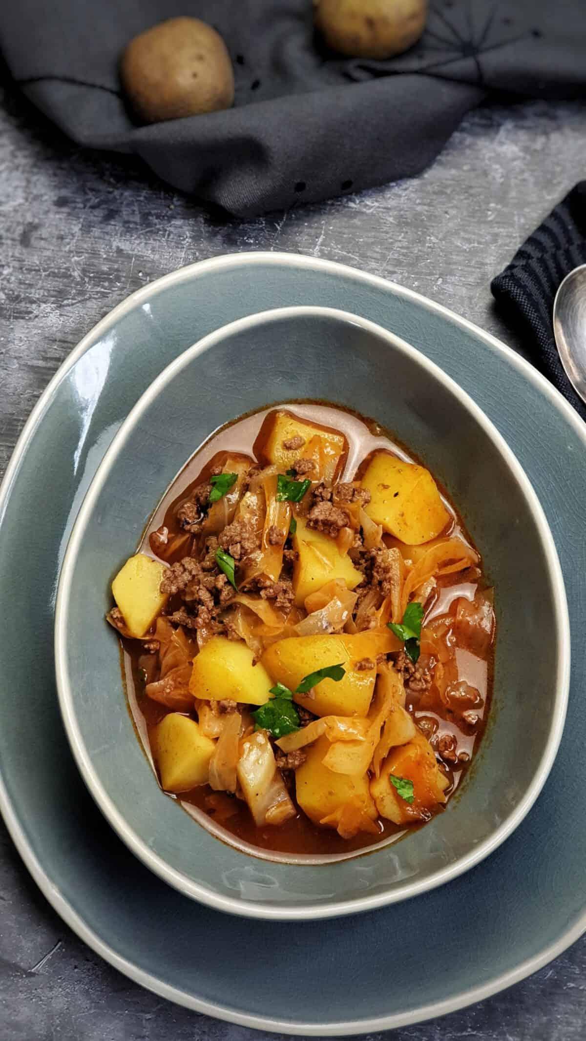 In einer blauen ovalen Schale ein Schichtkohl Gericht mit Kartoffeln und Hackfleisch.