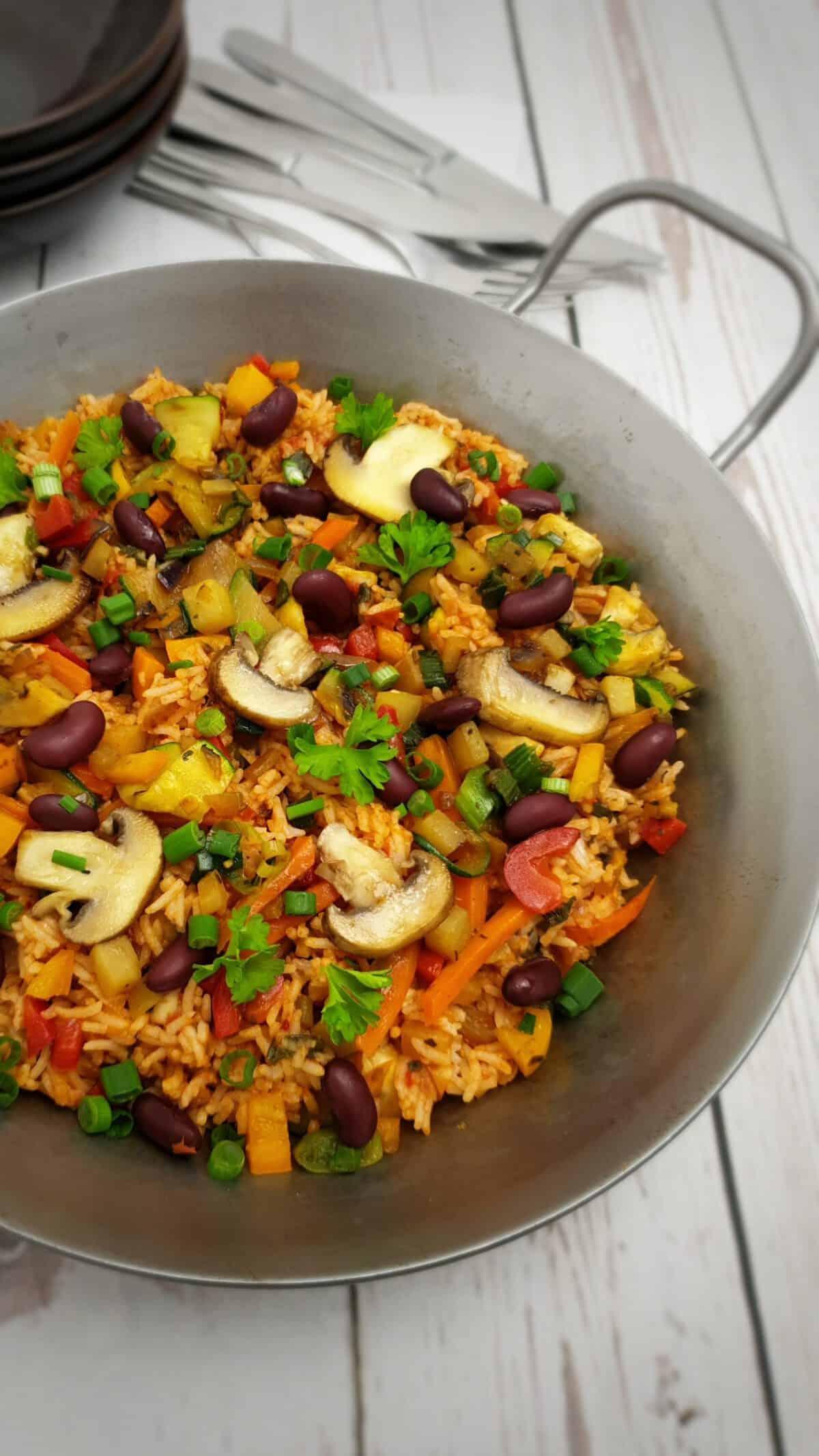 Vegetarische Gemüse-Pfanne mit Reis in einer gußeisernen Pfanne serviert.