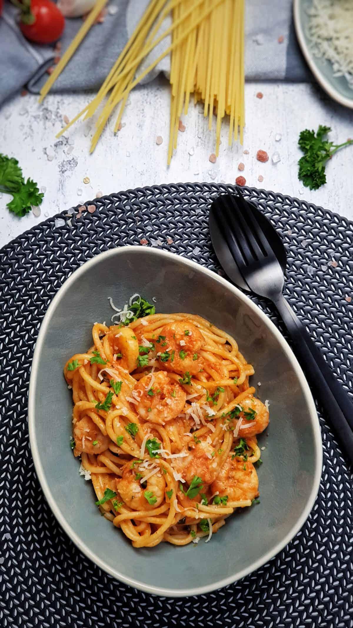 In einer blau grauen, ovalen Schale angerichtet Spaghetti mit Shrimps und Tomatensoße. Die Spaghetti sind mit Petersilie und Parmesan bestreut. Im Hintergrund Deko.