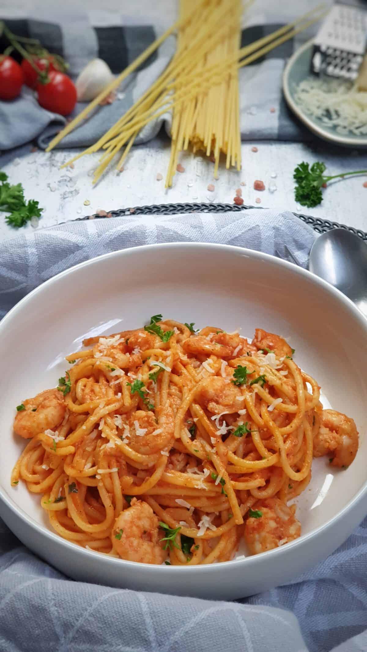 In einer weißen runden Schale angerichtet Spaghetti mit Garnelen und Tomaten-Soße. Die Spaghetti sind mit Petersilie und Parmesan bestreut. Im Hintergrund Deko.