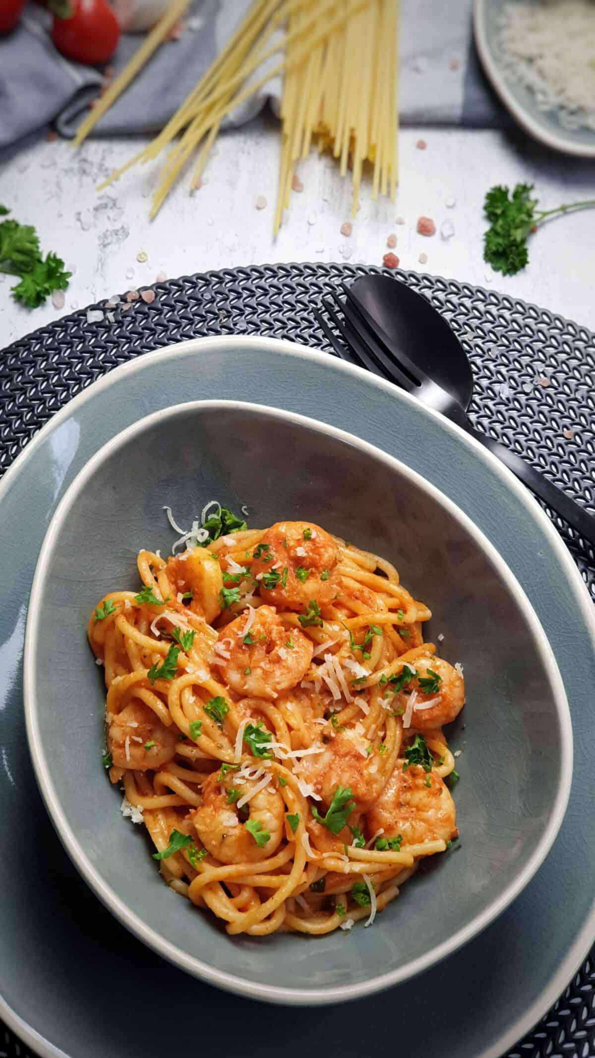 In einer ovalen blauen Schale Nudeln mit Tomaten-Soße und Garnelen. Mit Petersilie und Parmesan serviert.