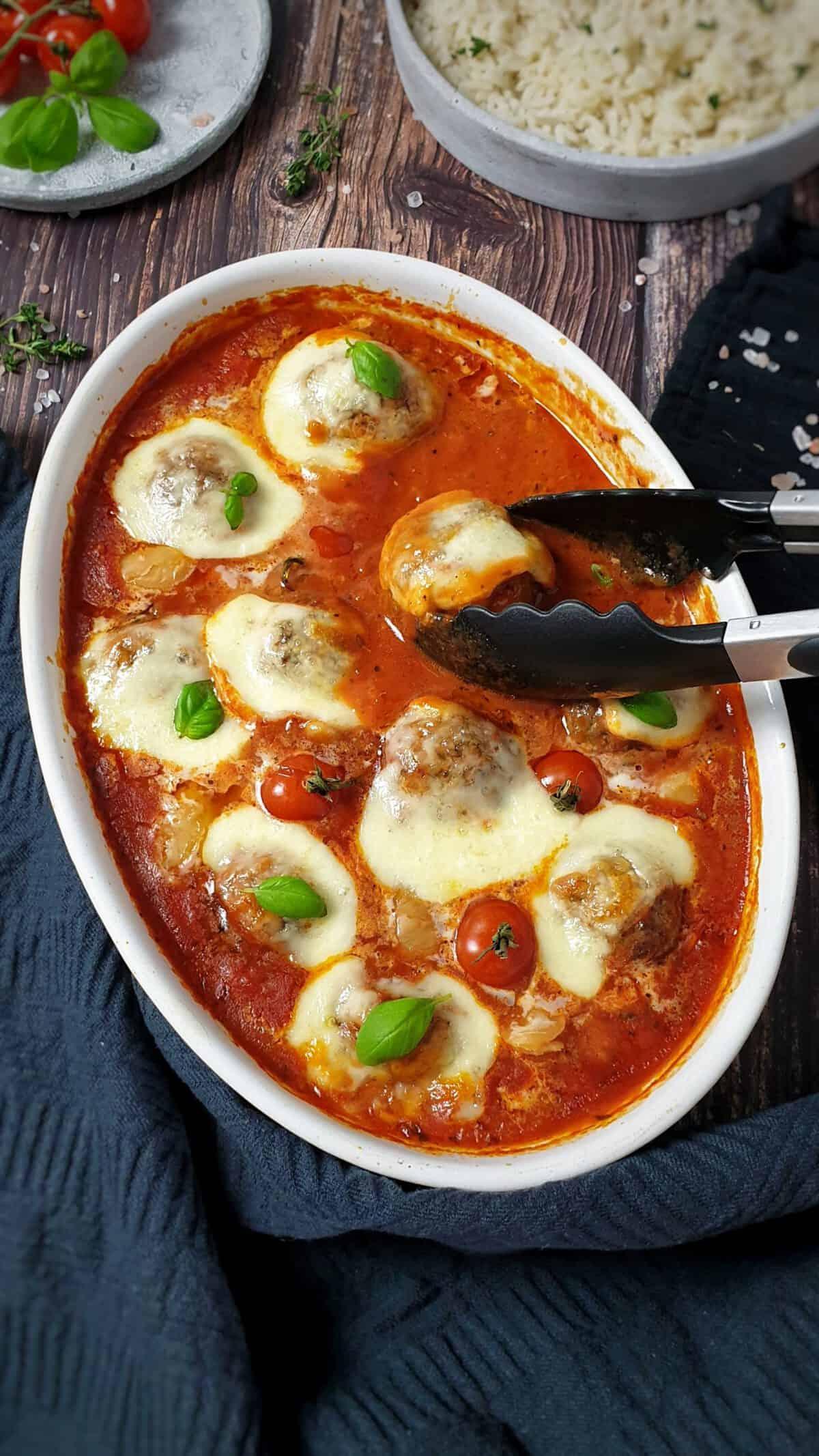 In einer weißen Auflaufform überbackene Ofen Hackbällchen mit Mozzarella in Tomatensoße.