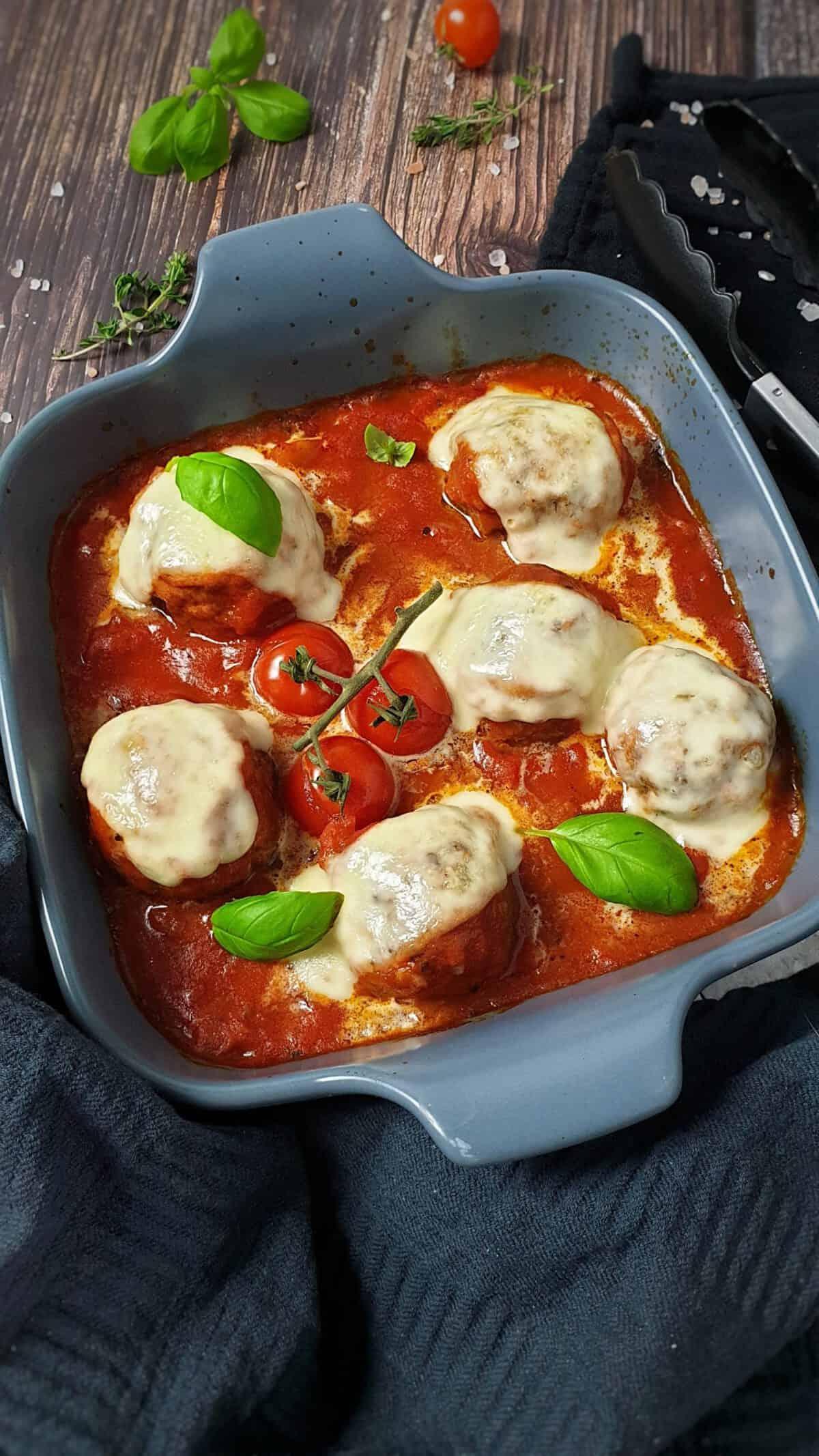 In einer grauen Auflaufform überbackene Ofen Hackbällchen mit Mozzarella in Tomatensoße.