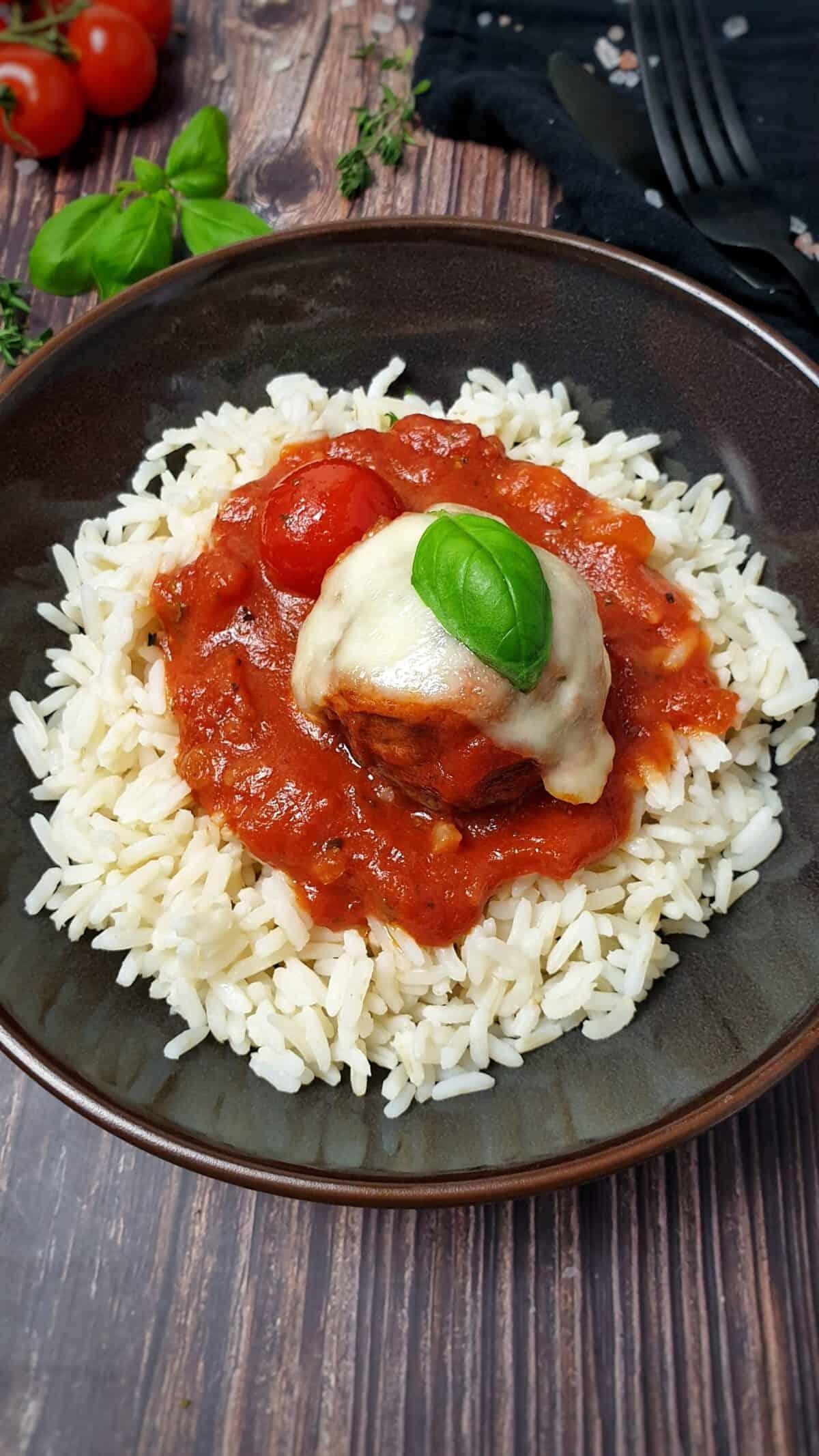 Hackfleischbällchen in Tomatensoße mit Mozzarella überbacken auf Reis angerichtet.