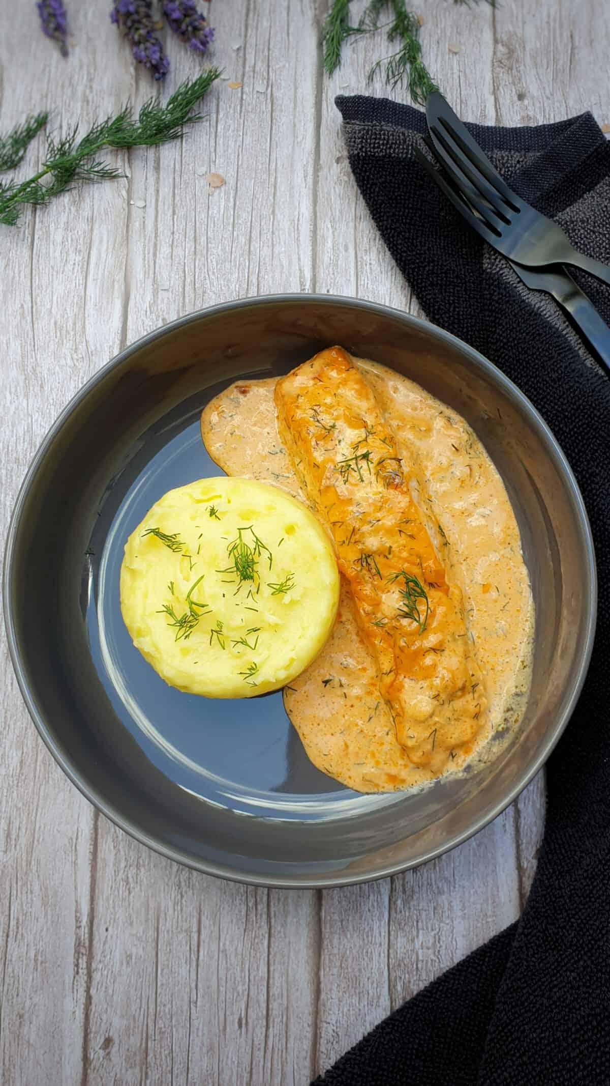 In einer grauen Schale angerichtet ein Lachsfilet in Sahne-Soße mit Kartoffelpüree. Im Hintergrund Deko.