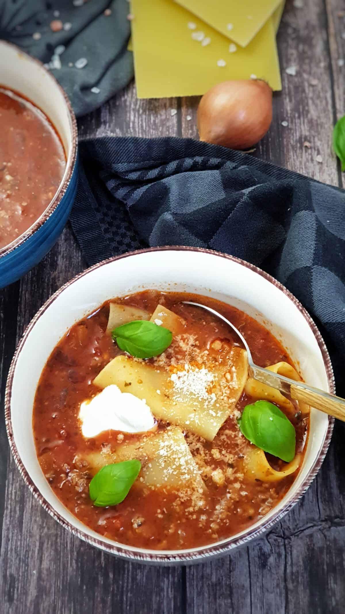 In einer weißen Schale angerichtet eine Lasagne Suppe mit Lasagne Platten, Creme Fraiche und Petersilie garniert.